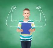Piccolo ragazzo sorridente dello studente con il libro blu Fotografia Stock Libera da Diritti