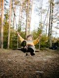 Piccolo ragazzo sorridente felice sveglio che oscilla in legno di autunno, concetto della gente di stile di vita Fotografia Stock Libera da Diritti