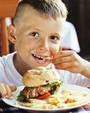 Piccolo ragazzo sveglio 6 anni con il maki delle patate fritte e dell'hamburger Immagine Stock Libera da Diritti