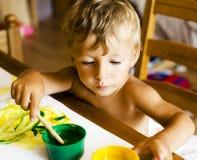 Piccolo ragazzo sveglio che dipinge a casa, fine di concetto della gente di stile di vita Fotografie Stock