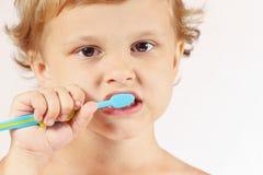 Piccolo ragazzo sveglio che pulisce i suoi denti Fotografie Stock Libere da Diritti