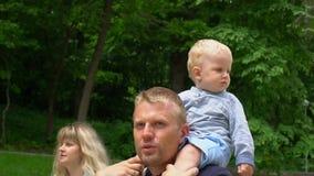 Piccolo ragazzo sveglio che si siede sul suo collo del ` s del padre nel giorno del ` s del padre del parco stock footage