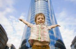 Piccolo ragazzo sveglio che sta la costruzione vicina di affari, sorridente Immagini Stock