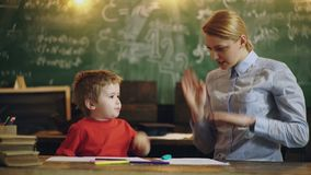 Piccolo ragazzo sveglio con il giovane insegnante che studia nell'aula e fa gli esercizi per resto a fondo di scuola verde video d archivio