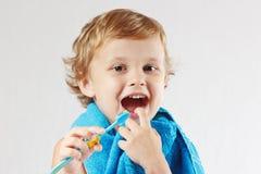 Piccolo ragazzo sveglio con il toothbrush con dentifricio in pasta Immagini Stock