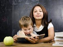Piccolo ragazzo sveglio con l'insegnante in aula, collocante alla tavola con i libri Fotografia Stock