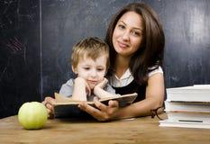 Piccolo ragazzo sveglio con l'insegnante in aula, collocante alla tavola con i libri Immagine Stock Libera da Diritti