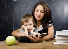 Piccolo ragazzo sveglio con l'insegnante in aula, collocante alla tavola con i libri Fotografia Stock Libera da Diritti