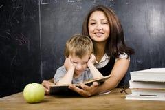 Piccolo ragazzo sveglio con l'insegnante in aula, collocante alla tavola con i libri Immagini Stock Libere da Diritti