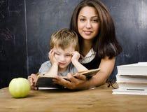 Piccolo ragazzo sveglio con l'insegnante in aula, collocante alla tavola con i libri Immagini Stock
