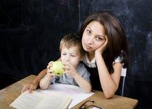 Piccolo ragazzo sveglio con l'insegnante in aula, collocante alla tavola con i libri Fotografie Stock Libere da Diritti