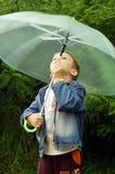 Piccolo ragazzo sveglio con l'ombrello di filatura Fotografia Stock