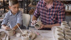 Piccolo ragazzo sveglio con suo padre che fa i vasi ceramici nelle terraglie stock footage