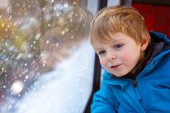 Piccolo ragazzo sveglio del bambino che guarda fuori la finestra del treno immagine stock