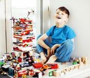 Piccolo ragazzo sveglio del bambino in età prescolare che gioca sorridere felice dei giocattoli a casa, Fotografia Stock