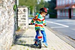 Piccolo ragazzo sveglio del bambino sulla bicicletta estate o il giorno del autmn Bambino felice in buona salute divertendosi con immagini stock
