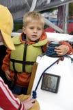 Piccolo ragazzo sveglio in giubbotto di salvataggio sull'yacht. fotografie stock libere da diritti