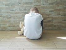 Piccolo ragazzo triste che si siede sul pavimento con un orsacchiotto solo Immagine Stock Libera da Diritti