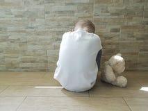 Piccolo ragazzo triste che si siede sul pavimento che dura con un orsacchiotto solo Fotografie Stock