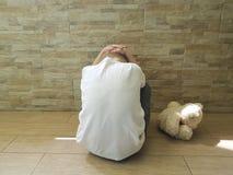 Piccolo ragazzo triste che si siede sull'uso del pavimento infelice un orsacchiotto solo Fotografia Stock Libera da Diritti