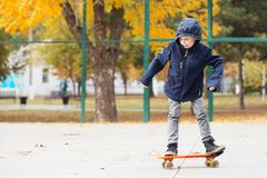 Piccolo ragazzo urbano con un pattino del penny Bambino che pattina in un autu Immagini Stock