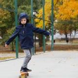 Piccolo ragazzo urbano con un pattino del penny Bambino che pattina in un autu Fotografie Stock