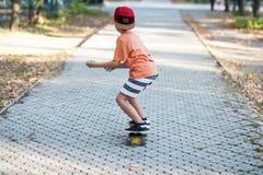 Piccolo ragazzo urbano con un pattino del penny Bambino che pattina in un summe Fotografie Stock Libere da Diritti