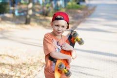 Piccolo ragazzo urbano con un pattino del penny Bambino che pattina in un summe Fotografie Stock