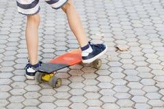 Piccolo ragazzo urbano con un pattino del penny Guida del ragazzino in Th Fotografia Stock