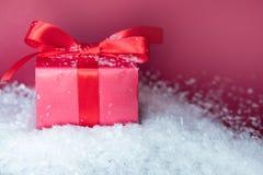 Piccolo regalo con l'arco rosso in neve su fondo rosa Spazio libero per il vostro testo fotografie stock