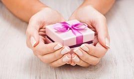 Piccolo regalo in mani delle donne Immagini Stock