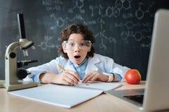 Piccolo ricercatore colpito che esprime le emozioni in laboratorio Fotografia Stock