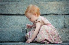 Piccolo ritrovamento sveglio del bambino qualcosa sulla terra Fotografia Stock