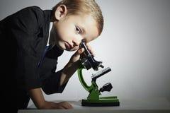 Piccolo scienziato che guarda in microscopio Little Boy Bambino Istruzione Immagine Stock