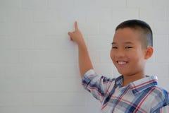 piccolo scolaro asiatico dei bambini del bambino del ragazzo del bambino che sorride & che indica immagine stock libera da diritti