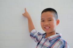 piccolo scolaro asiatico dei bambini del bambino del ragazzo del bambino che sorride & che indica fotografia stock