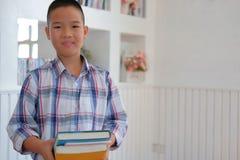 piccolo scolaro asiatico dei bambini del bambino del ragazzo del bambino che tiene i libri 'chi' fotografia stock
