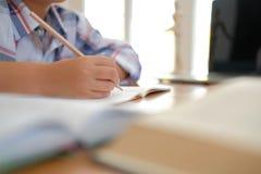 piccolo scolaro asiatico del ragazzo del bambino che scrive attingendo taccuino Chil fotografie stock