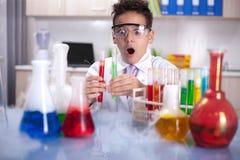 Piccolo scolaro che lavora nel laboratorio di chimica Immagini Stock