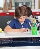 Piccolo scolaro che studia allo scrittorio Immagini Stock Libere da Diritti