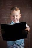 Piccolo scolaro con capelli biondi in un vestito piacevole, Immagine Stock