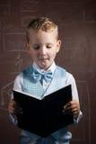 Piccolo scolaro con capelli biondi in un vestito piacevole, Immagini Stock Libere da Diritti