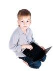 Piccolo scolaro con il computer portatile isolato su bianco Immagine Stock