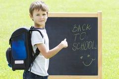 Piccolo scolaro contro la lavagna Istruzione, di nuovo al concetto della scuola Fotografie Stock