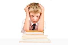 Piccolo scolaro faticoso che si siede alla tabella Fotografia Stock Libera da Diritti