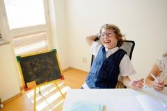 Piccolo scolaro impertinente di vetro nelle risate allegramente Fotografie Stock Libere da Diritti