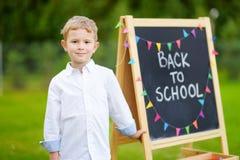Piccolo scolaro sveglio che ritiene eccitato circa ritornare a scuola Immagine Stock Libera da Diritti
