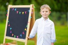 Piccolo scolaro sveglio che ritiene eccitato circa ritornare a scuola Fotografia Stock