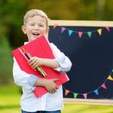 Piccolo scolaro sveglio che ritiene eccitato circa ritornare a scuola Fotografia Stock Libera da Diritti