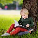 Piccolo scolaro sveglio che si siede nell'ambito dell'albero e dello studio Di nuovo a Immagini Stock Libere da Diritti